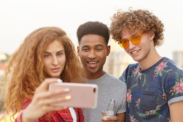 Vrienden nemen selfie met behulp van een mobiele telefoon