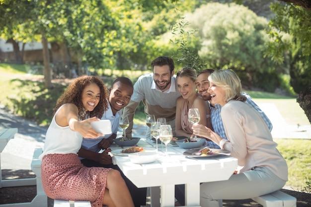 Vrienden nemen selfie op mobiele telefoon tijdens het eten