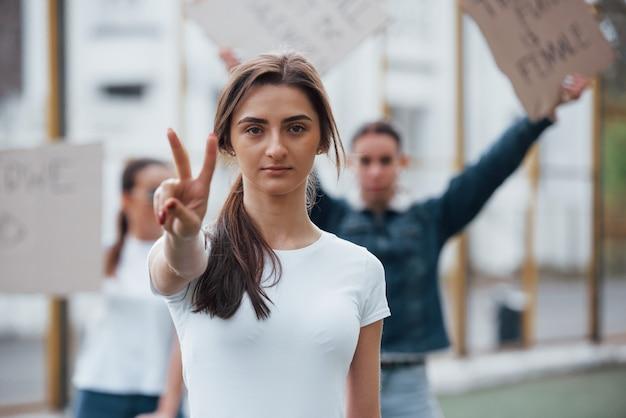 Vrienden op de achtergrond. een groep feministische vrouwen protesteert buitenshuis voor hun rechten