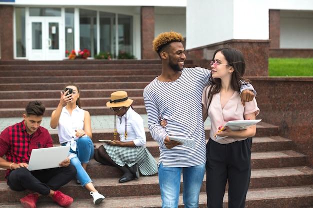 Vrienden op de trap van de universiteit omringen