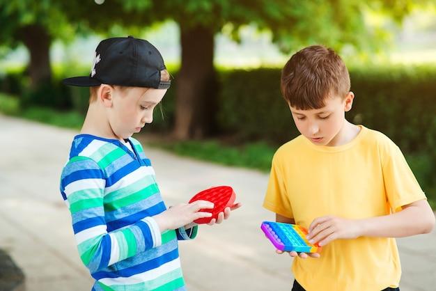Vrienden op een wandeling met siliconen bubbelspeelgoed. jongens die buiten plezier hebben. modern antistress speelgoed voor kinderen.