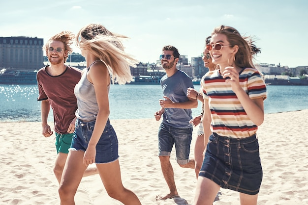 Vrienden op het strand, gelukkige jonge vriendengroep, hebben plezier en vieren tijdens het springen en