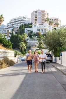 Vrienden op zomervakantie, lachen, plezier maken, springen, wandelen door de straten van de stad.