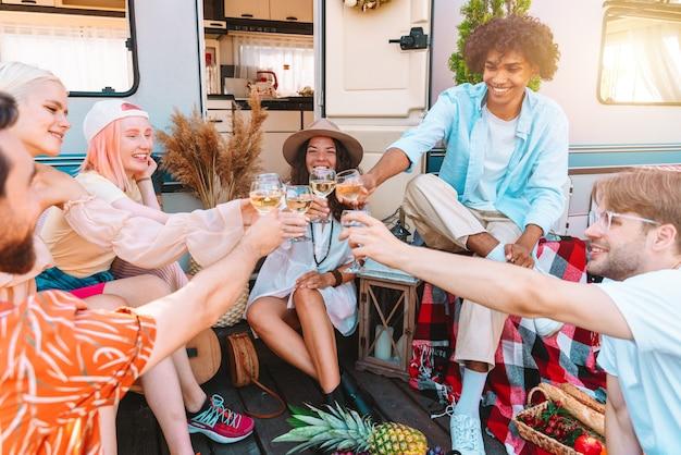Vrienden picknicken en proosten met wijn