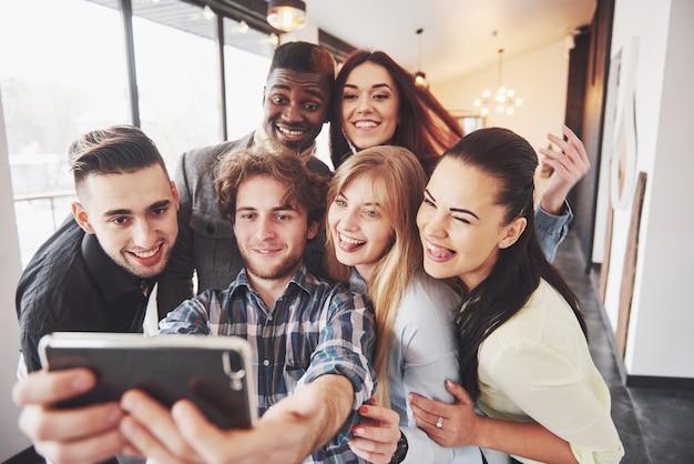 Vrienden plezier in restaurant. drie jongens en drie meisjes maken selfie en lachen. op de voorgrond jongen met slimme telefoon. ze dragen allemaal vrijetijdskleding