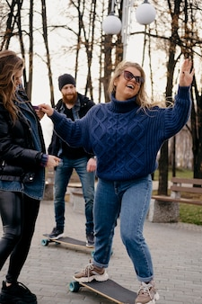 Vrienden plezier skateboarden buiten in het park