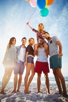 Vrienden poseren met ballon op zand