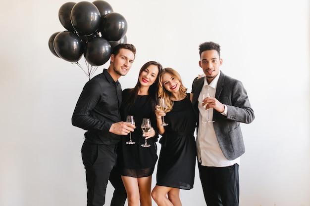 Vrienden poseren op feestje met champagneglazen en zwarte ballonnen