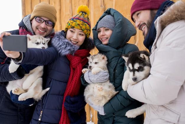 Vrienden poseren voor foto met puppy's