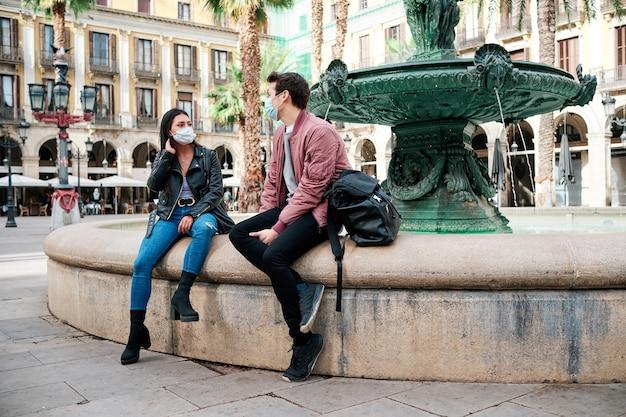 Vrienden praten buiten met hun gezichtsmaskers op.