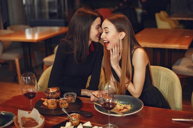 Vrienden praten en plezier hebben op etentje. elegant geklede vrouwen van mensen die aan het dineren zijn.