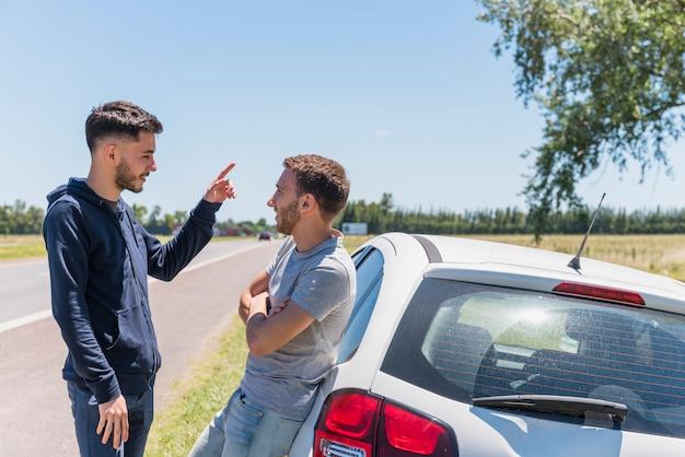 Vrienden praten naast de weg