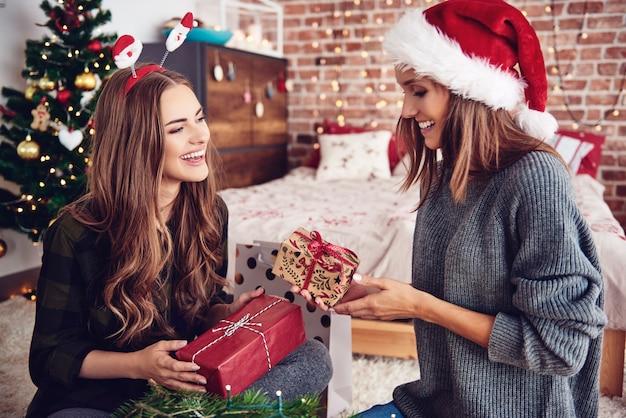 Vrienden presenteren geschenken elkaar in de slaapkamer