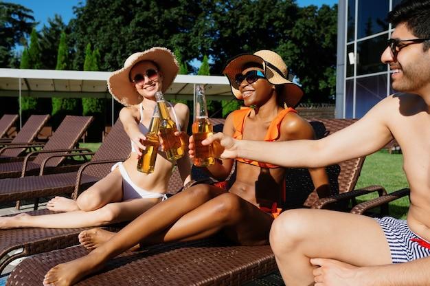 Vrienden rammelen flessen met bier bij het zwembad. gelukkige mensen die plezier hebben op zomervakanties, vakantiefeest bij het zwembad buiten. een man en twee vrouwen zonnebaden