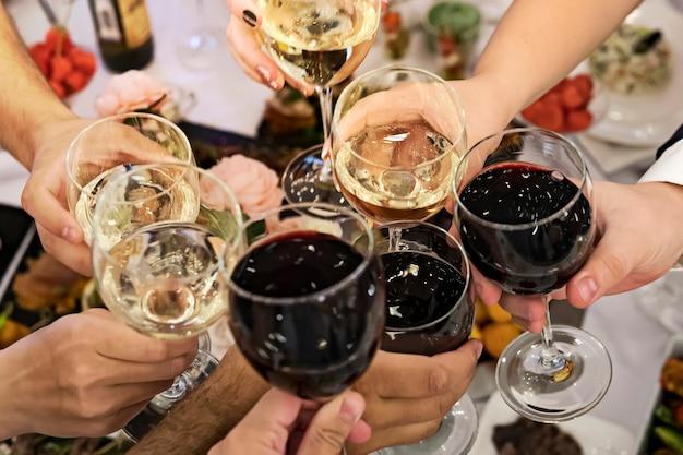 Vrienden rammelende glazen boven de eettafel bij een feestelijke gelegenheid. mensen drinken toast en klinken tuimelaars tijdens een formeel etentje. drinken bij een banket. mannen en vrouwen vieren een evenement.