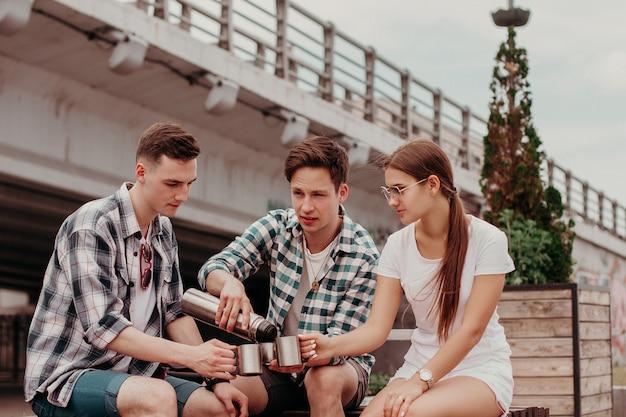 Vrienden-reizigers die thermos gebruiken tijdens een zomerse wandeling door de stad