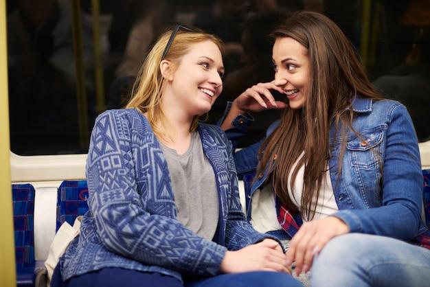 Vrienden roddelen in de metro