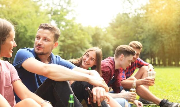 Vrienden roosteren bier op barbecue in de natuur.