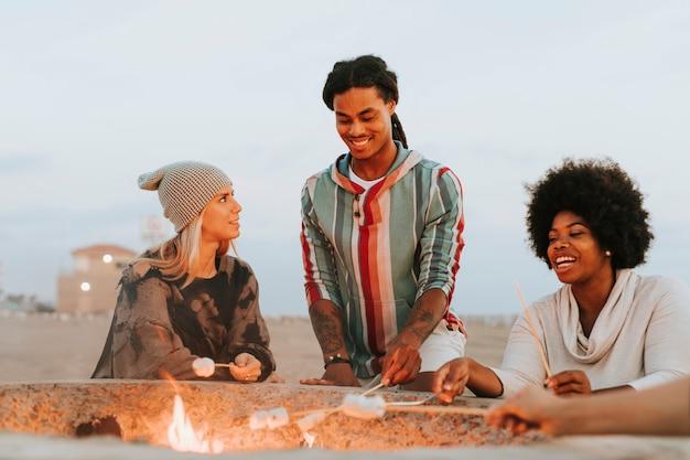 Vrienden roosteren marshmallows op het strand