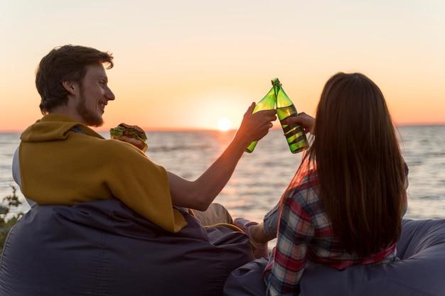 Vrienden roosteren met bier buiten bij zonsondergang