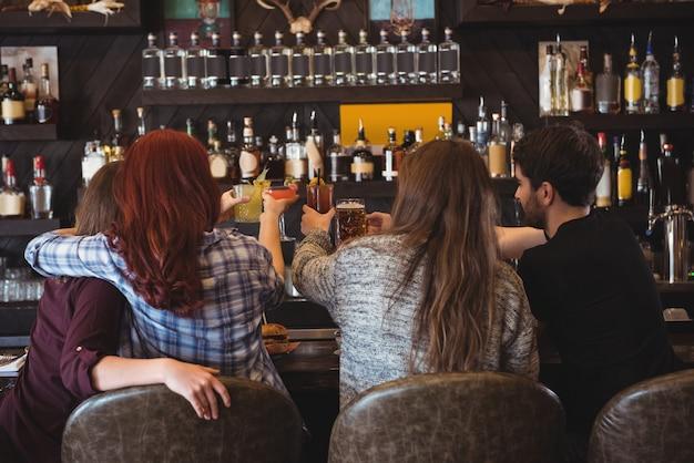 Vrienden roosteren met bier en cocktailglazen in staaf
