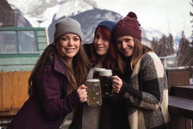 Vrienden roosteren met bierglazen in staaf