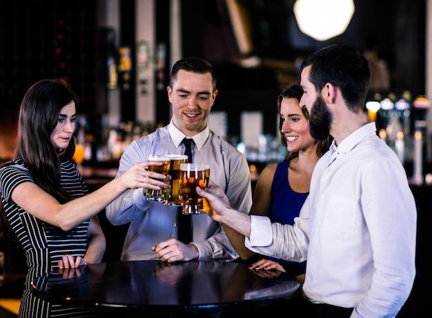 Vrienden roosteren met een biertje in een bar