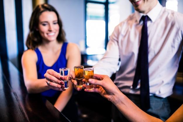 Vrienden roosteren met schoten in een bar