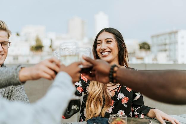 Vrienden roosteren tijdens een feest op het dak