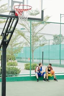 Vrienden rusten na een spelletje basketbal