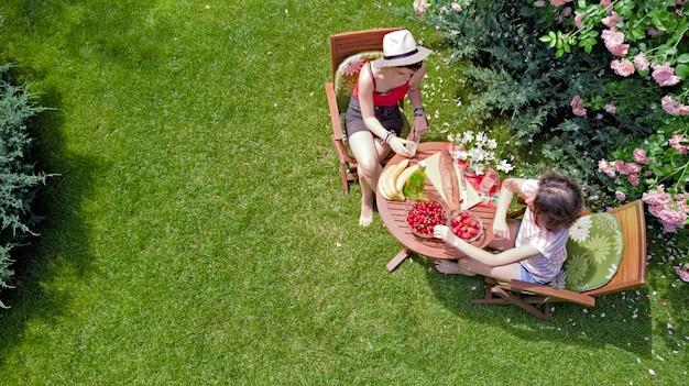 Vrienden samen buiten eten in de zomertuin, meisjes hebben picknick in het park, luchtfoto van tafel met eten en drinken van bovenaf
