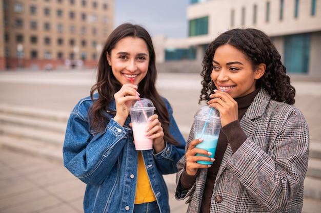 Vrienden samen buiten met milkshakes