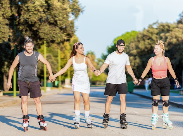 Vrienden schaatsen op inline skates hand in hand op een straat met bomen