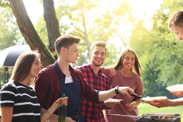 Vrienden slaan de handen ineen tijdens een barbecue in de natuur.