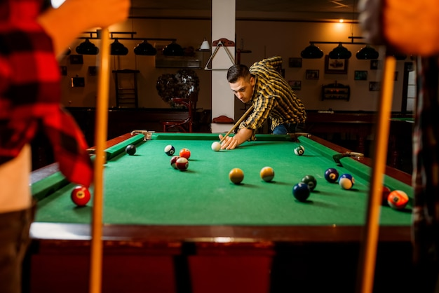 Vrienden speelt amerikaans biljart in de biljartkamer. groep speelt poolspel in sportbar, biljartkamer interieur op achtergrond