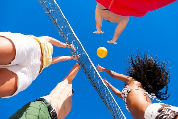 Vrienden spelen beachvolleybal