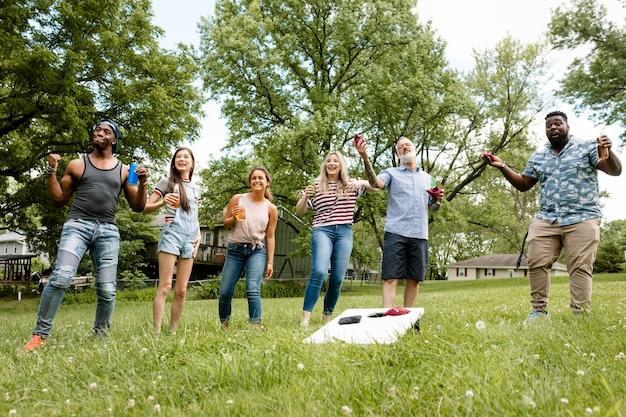 Vrienden spelen cornhole op een zomerfeest in het park