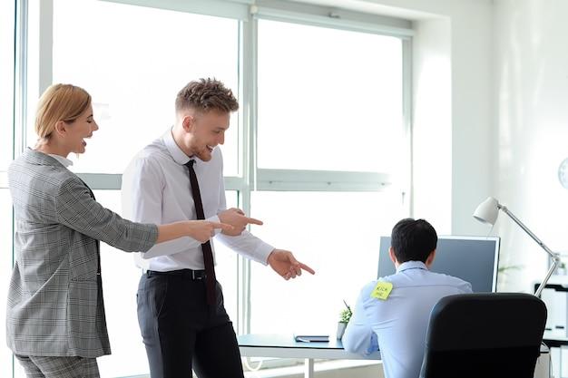 Vrienden spelen een grap met hun collega op kantoor. april fools 'day-grap