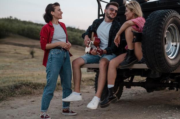 Vrienden spelen gitaar tijdens het reizen met de auto