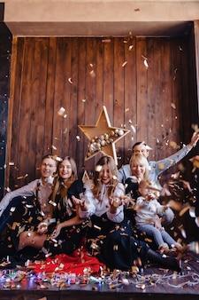 Vrienden spelen met confetti op nieuwjaarsviering, huisatmosfeer, kerstmis