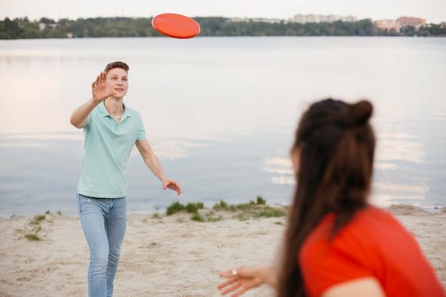 Vrienden spelen met frisbee op het strand