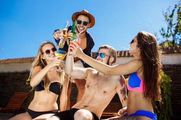 Vrienden spreken, glimlachen, cocktails drinken, rusten, ontspannen bij het zwembad.
