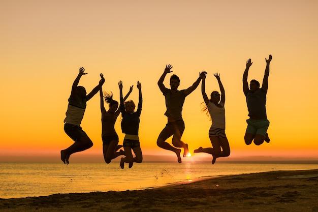 Vrienden springen op het strand aan zee bij zonsondergang
