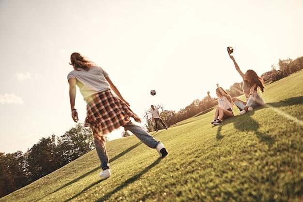 Vrienden steunen. twee jonge vrouwen die op het gras zitten en gebaren maken terwijl hun mannelijke vrienden buiten voetballen