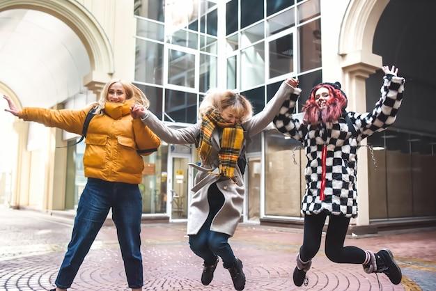 Vrienden tieners studenten met schoolrugzakken, plezier hebben op weg van school en springen. het stadsoppervlak