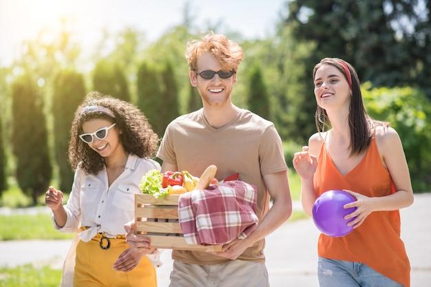 Vrienden, tijdverdrijf. drie jonge gelukkige vrienden in vrijetijdskleding met bal en mand met eten wandelen op picknick in zonnig groen park
