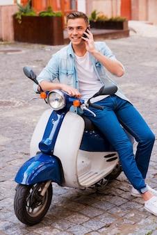 Vrienden uitnodigen voor een ritje. vrolijke jonge man zittend op een scooter en praten op de mobiele telefoon