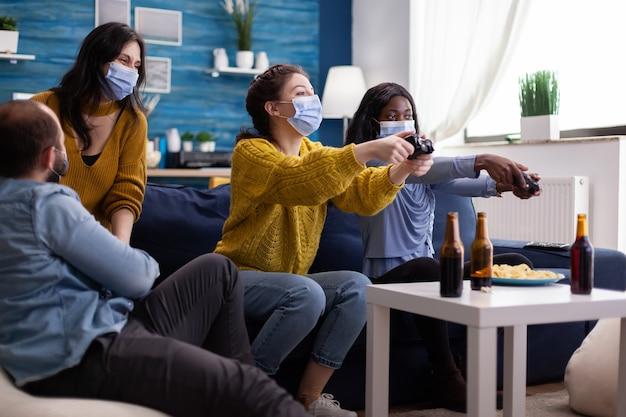 Vrienden van gemengd ras ontmoeten elkaar om videogames te spelen met een draadloze controller die een gezichtsmasker draagt om te voorkomen dat ze ziek worden met corona in de tijd van een sociale pandemie. groep mensen die samen van tijd genieten.