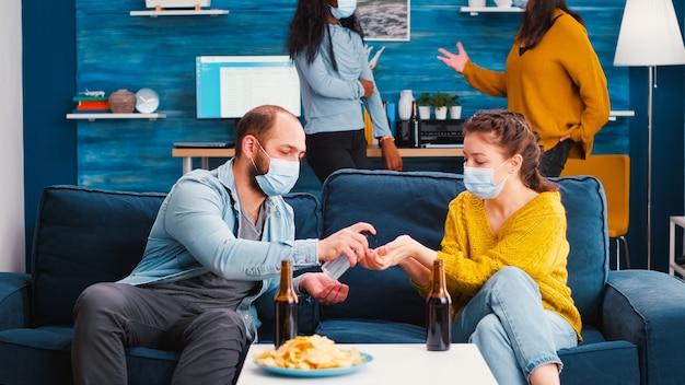 Vrienden van gemengde rassen met medische maskers handen desinfecteren met ontsmettingsgel tijd samen doorbrengen in de woonkamer
