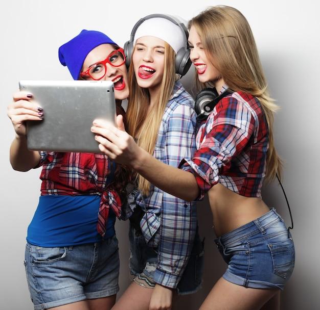 Vrienden van hipstermeisjes die selfie met digitale tablet over grijze achtergrond nemen